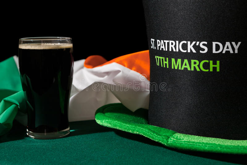 Closeup of St Patrick day with a pint of black beer, hat and irish flag. Over a green table and black background royalty free stock image