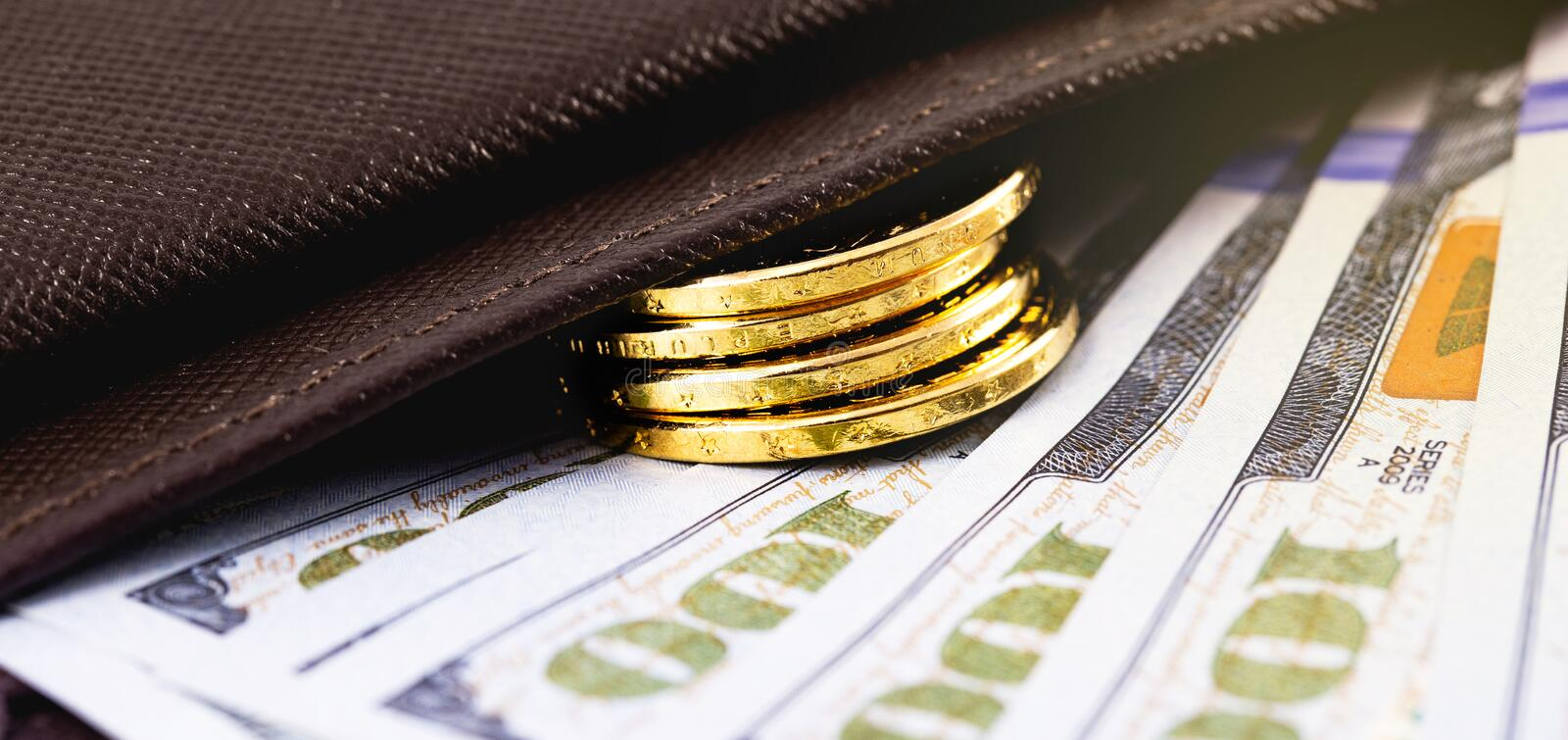 Stack golden metal coins. Closeup stack golden metal coins and dollars in wallet royalty free stock photo