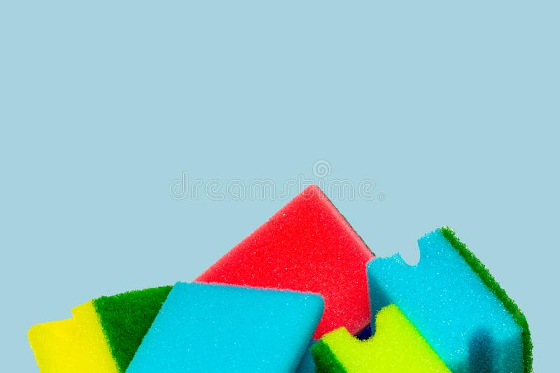 Close-up of a stack or heap of various colorful sponges or scouring pads isolated on a blue background. Household chore concept. stock photography