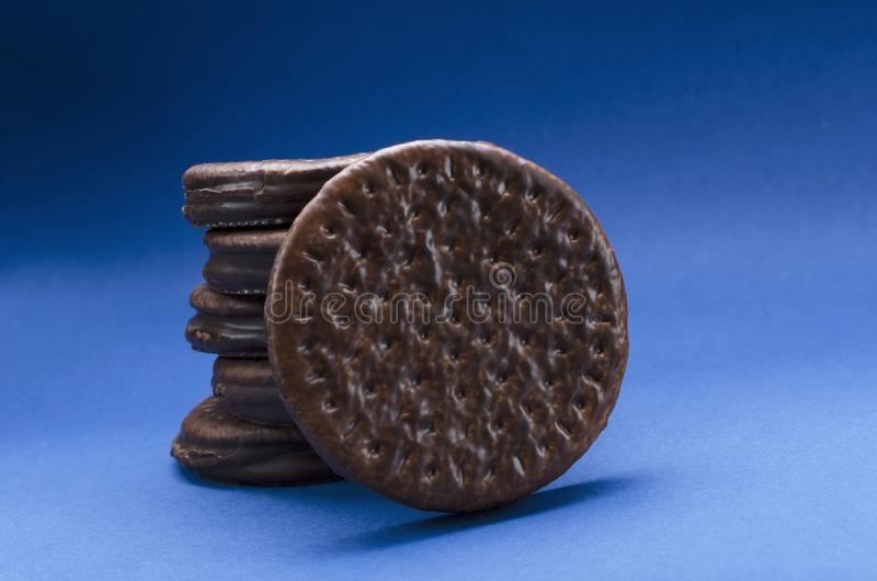 Closeup of stacked round cookies with chocolate glaze on the blue background. Top view of delicious chocolate biscuits on the blue surface royalty free stock photos