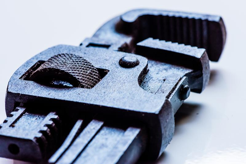 Black stained Pipe Wrench handtool. Closeup of stained pipe wrench hand tool in isolated white background royalty free stock photo