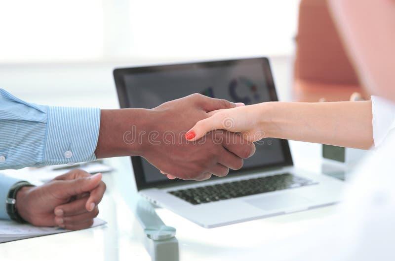 closeup starka finansiella partners som skakar händer över ett skrivbord royaltyfria bilder