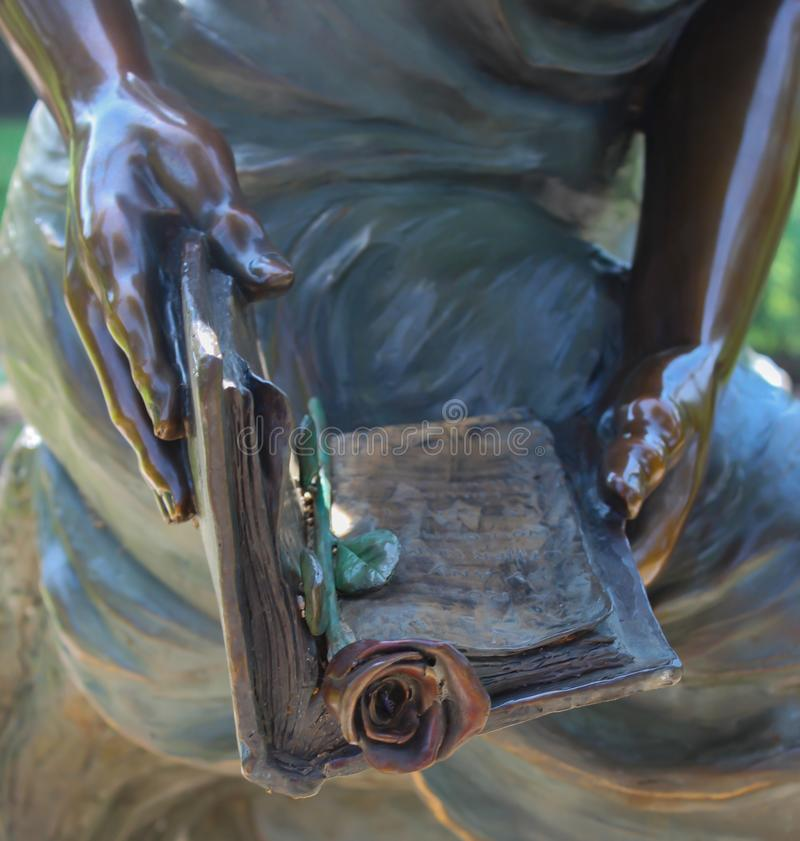Closeup of statue hands holding book bookmarked with a rose royalty free stock photo
