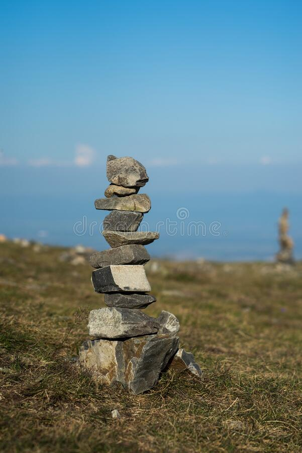 stone balance at the top of the mountain on blue sky background stock photography