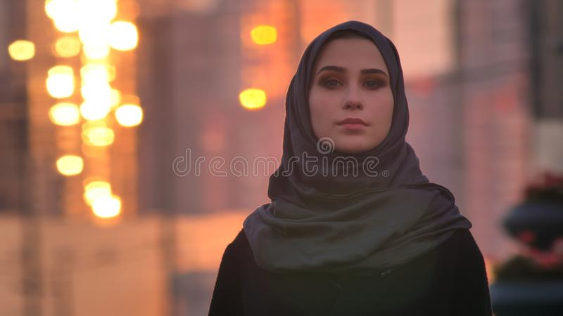 Closeup straight portrait of young pretty female in hijab looking forward at camera with urban city and shining royalty free stock images