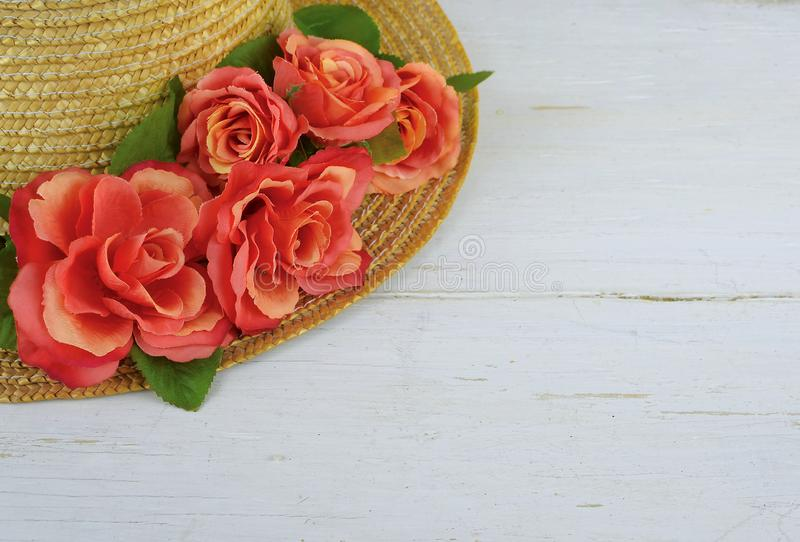 Closeup of a straw bonnet decorated with multiple silk roses on a white washed wooden background with copy space. Good for spring. Summer, wedding or Kentucky royalty free stock photography