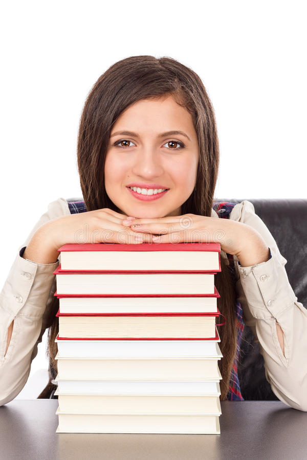 Closeup of student holding her head on a stack of books stock photo