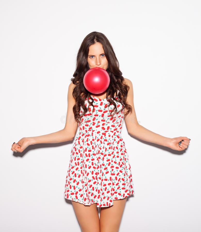 Closeup studio portrait of beautiful brunette girl blowing a red balloon wearing short cherry dress and spread her arms to the sid stock image