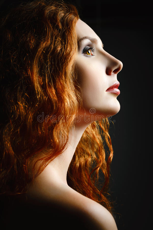 Closeup studio portrait of beautiful redhead woman stock photo