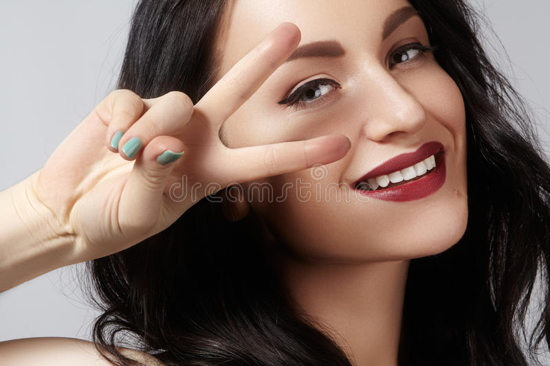 Closeup studio portrait of beautiful young woman with gesturing peace. Perfect style and make-up. happy toothy smile royalty free stock images