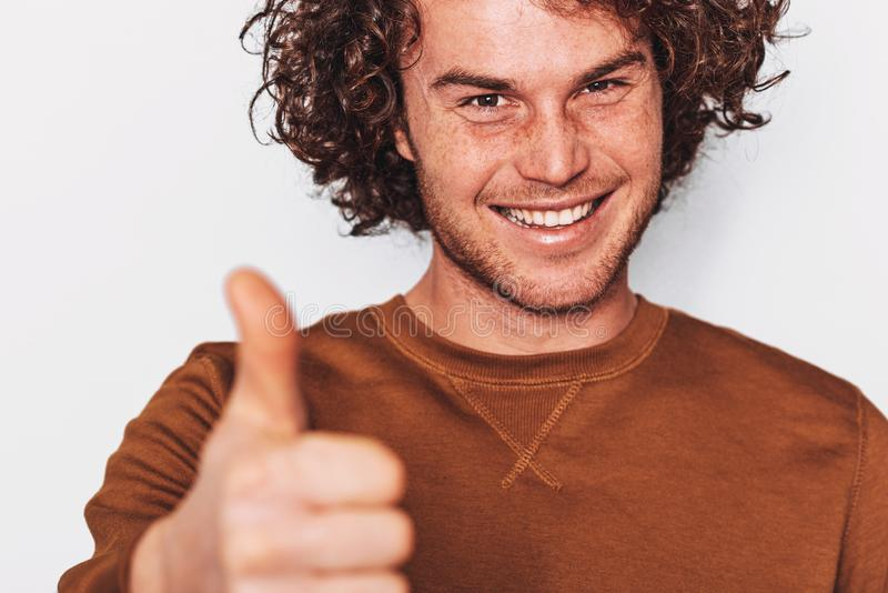 Closeup studio portrait of handsome man smiling with curly hair, posing for social advertisement with thumb up on white wall. stock photos
