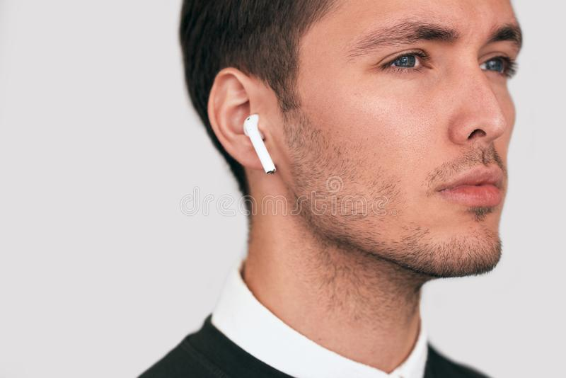 Closeup studio portrait of serious young handsome man posing with wireless earphones on white studio background. royalty free stock images