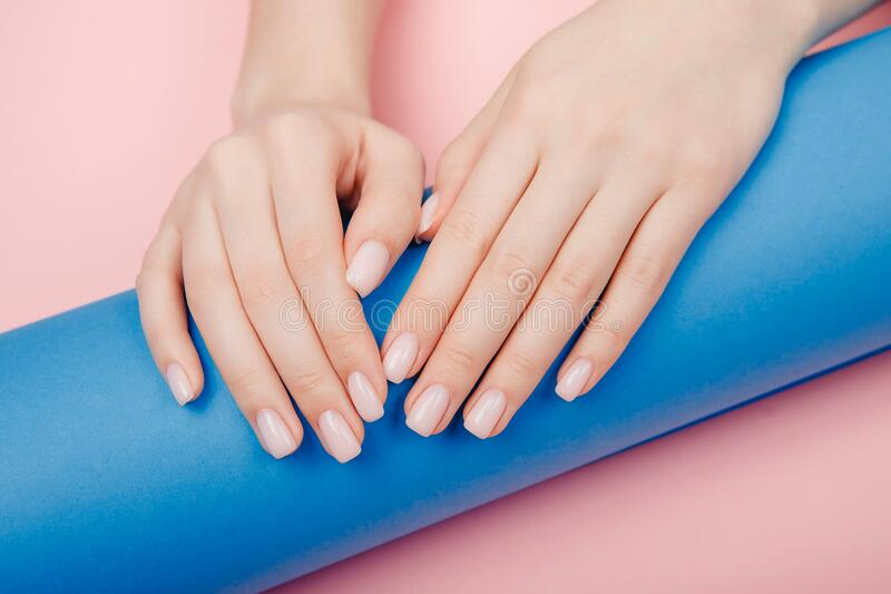 Closeup Stylish trendy nail manicure woman hands on pink and blue background, top view royalty free stock photos