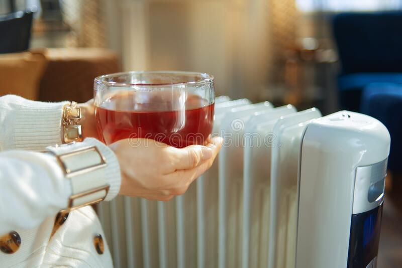 Closeup on stylish woman holding cup of hot tea near radiator. Closeup on stylish 40 years old housewife in the modern house in sunny winter day holding cup of stock image