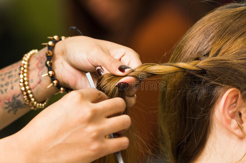 Closeup stylist hands working with brunette hair stock image