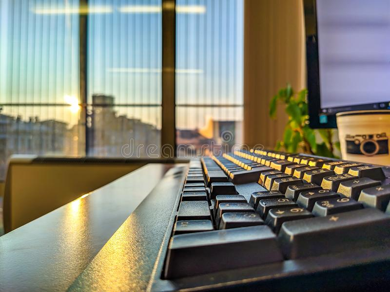 Closeup of a sun shining through huge windows at an office on a black keyboard on a new another day at a job stock photo