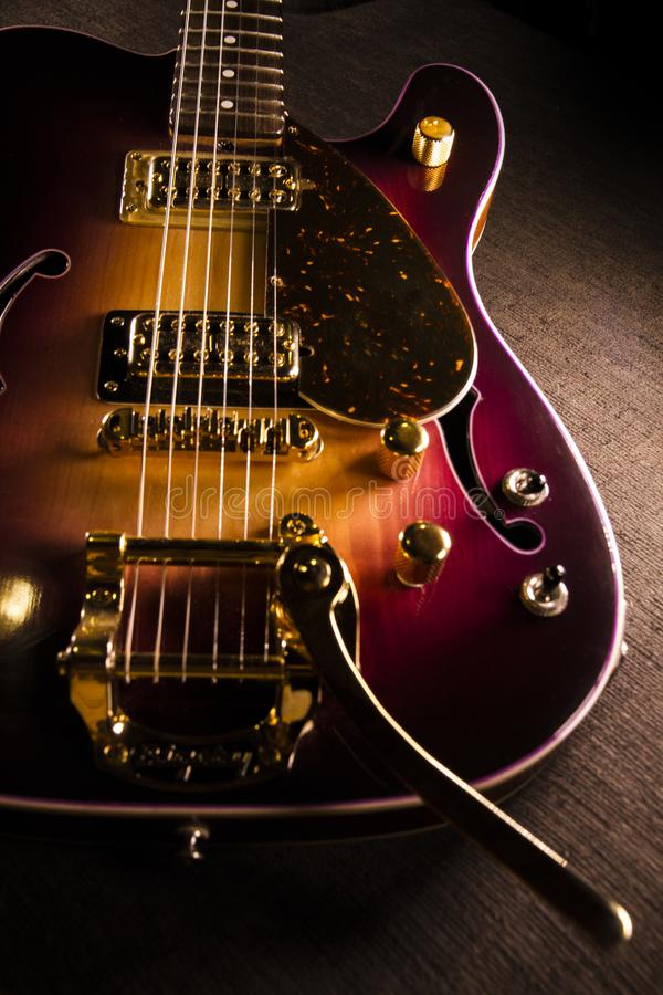 Closeup of sunburst electric guitar with brass mechanics and bright colors on a dark shaded background stock photos