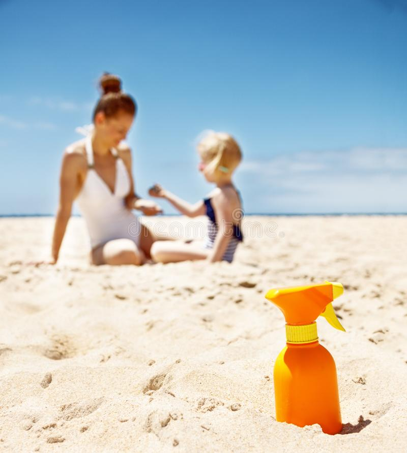 Closeup on sunscreen bottle on beach. Family in background stock image