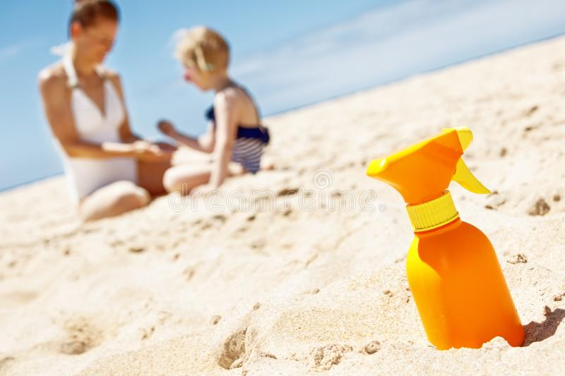 Closeup on sunscreen bottle on beach. Family in background stock photo