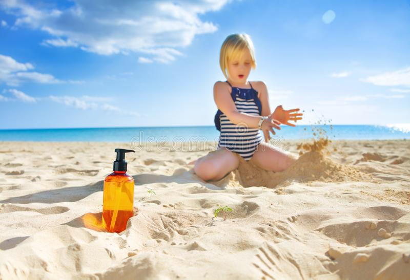 Closeup on sunscreen bottle and child playing in background stock images