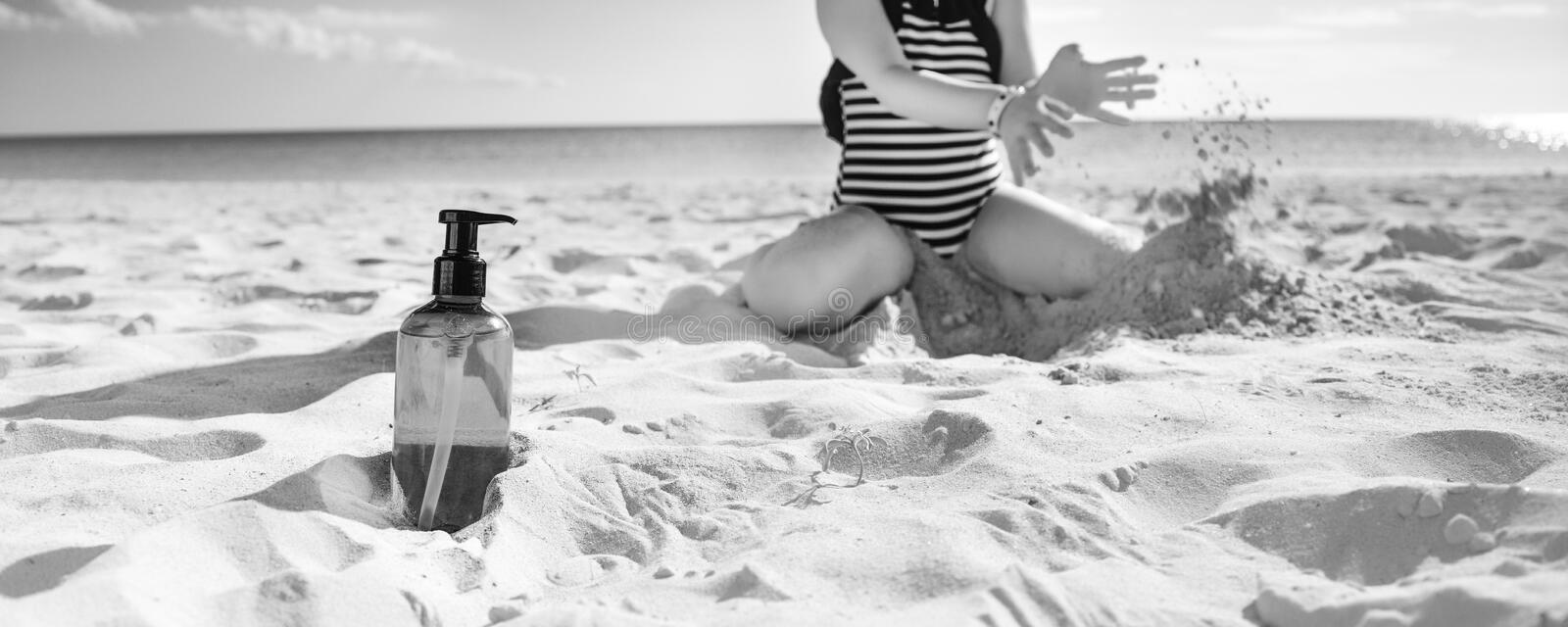 Closeup on sunscreen bottle and child playing in background stock photos