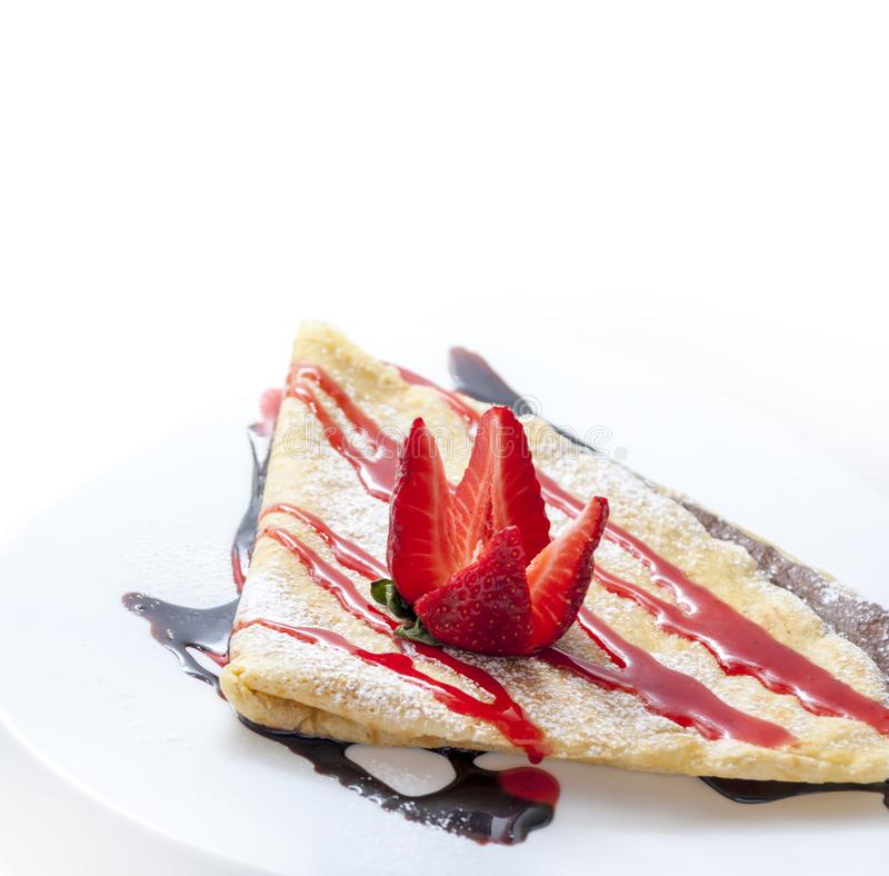 Closeup of sweet french crepes with chocolate and strawberry syrup on restaurant plate. Sweet dessert food with fruit and carame royalty free stock photography