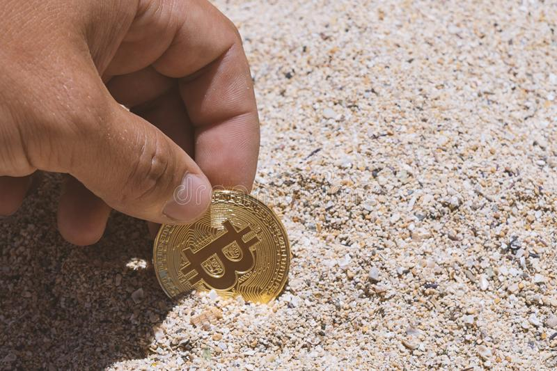 Closeup of a symbolic bitcoin coin in the sand in man hand. Bitcoin mining concept stock photo