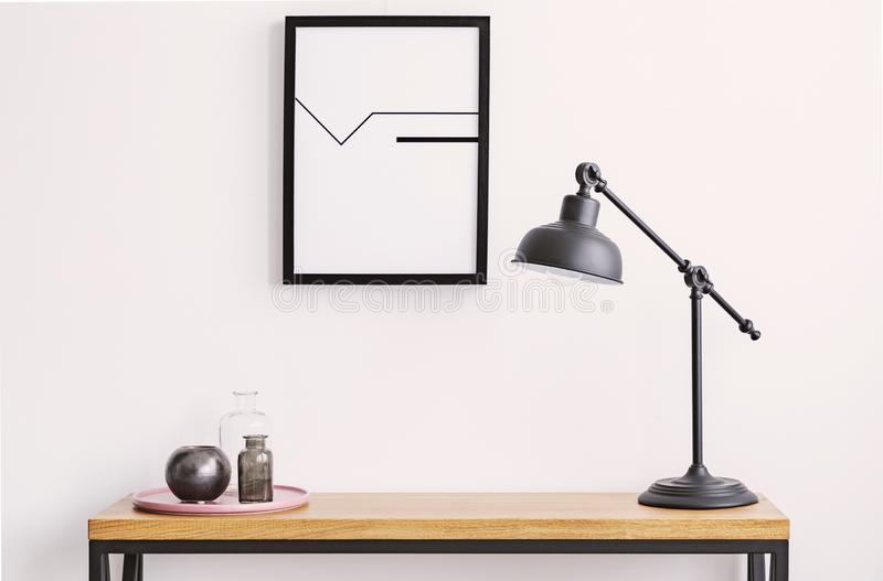 Closeup of table with lamp and plate with glass bottles, poster in black frame on white wall. Above royalty free stock image
