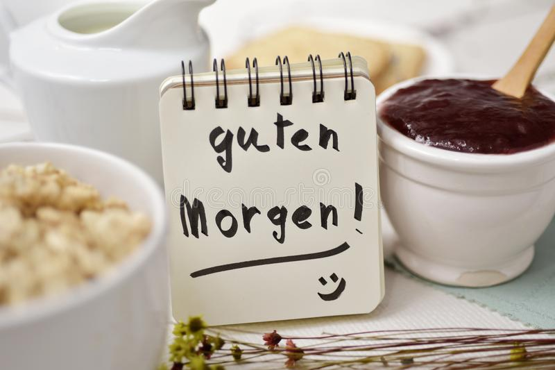 Breakfast and text good morning in german. Closeup of a table set for breakfast with a porcelain bowl with cereals, some toasts, a bowl with jam and a note with stock photos