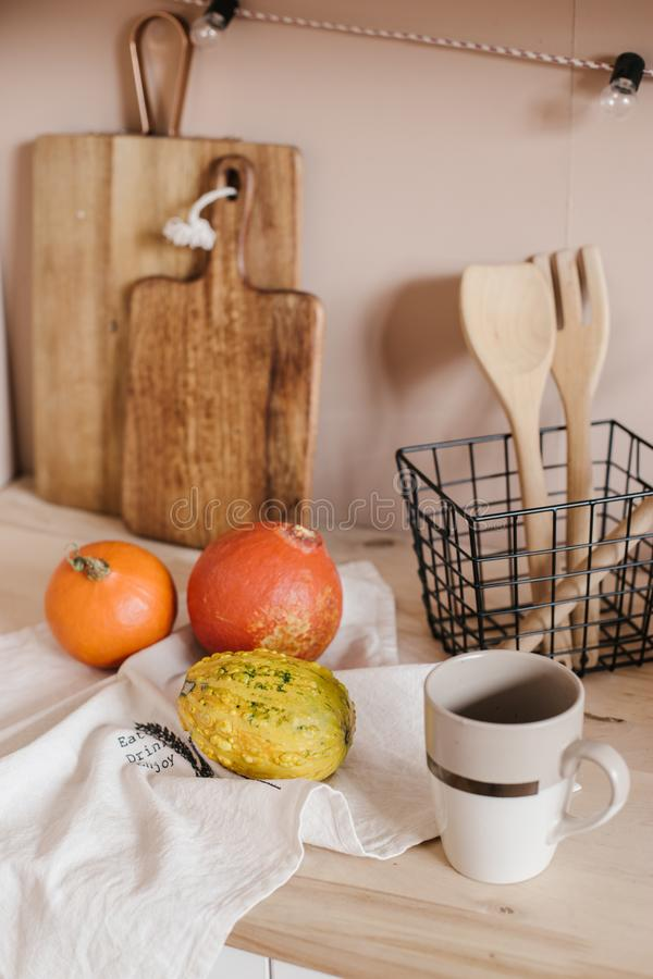 Kitchen beige interior. Table and pumpkins and cup on it royalty free stock image