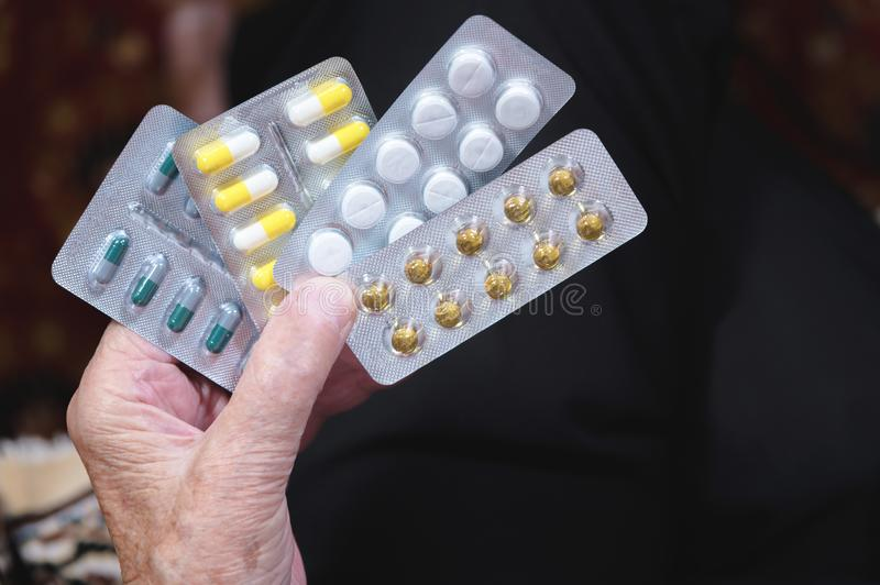 Closeup of a tablet on the hands of an old woman. The concept of choosing medication in old age stock photos