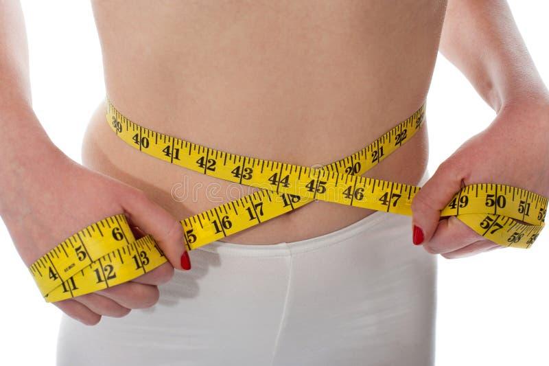 Closeup of tape measure around woman waist stock photos