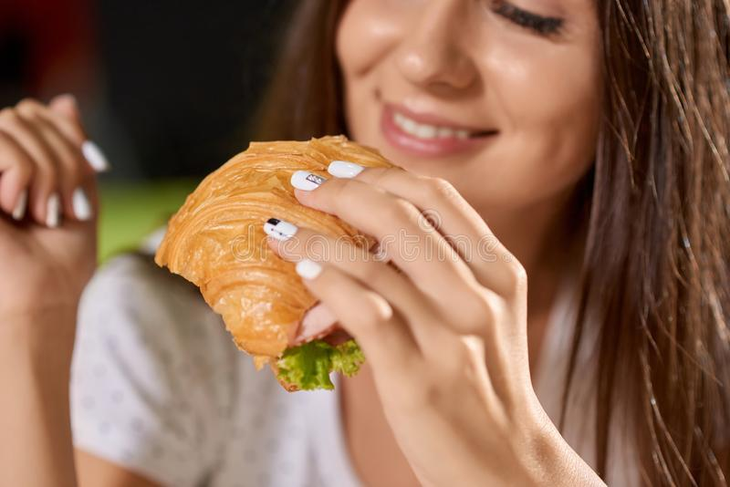 Closeup of tasty croissant in hands of pretty girl. Closeup of tasty croissant with greens and ham in hands of pretty girl. Smiling woman keeping snack, eating royalty free stock photography