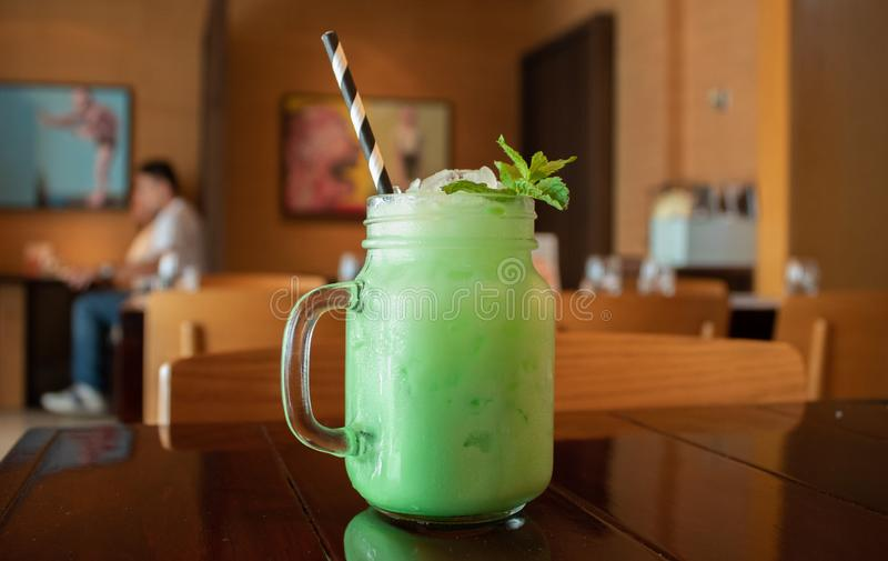 Closeup of a tasty mint Thai milk tea on a wooden table at a cafe with a blurred background stock photo
