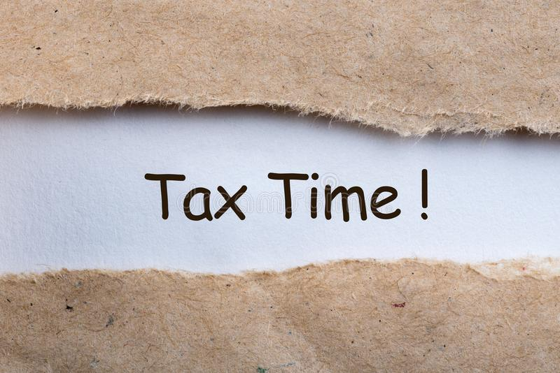 Closeup of Tax Time written on yellow paper note in a torn envelope. Tax planning and budgeting concept.  stock photos