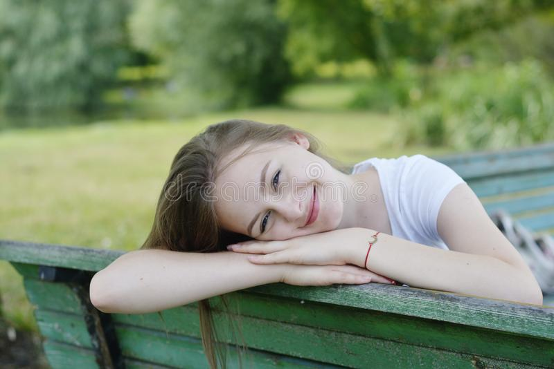 Closeup of teenage girl sitting, relaxing in the park, on a bench. Education, school girl. Smiling young woman. Summer time, stock photos