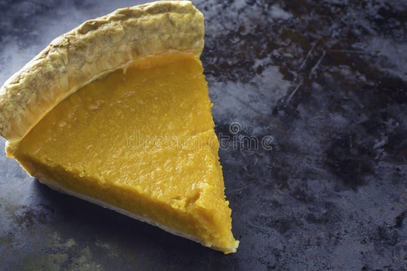 Slice of sweet potato pie on dark background. Closeup tempting slice of sweet potato pie on black background; delicious dessert stock photos