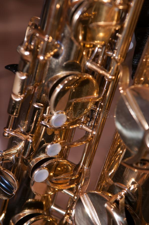 Closeup on Tenor Saxophone Keys. Against blurred brown background royalty free stock image