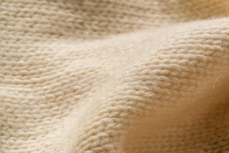 The closeup texture of cashmere things. Macro shot of knitted fabric from Lana Wool threads. Warm winter clothes. Background textile surface with copy space stock photos