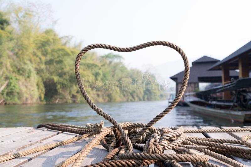 Closeup thick rope tie the heart shape on the wooden terrace near river stock photo