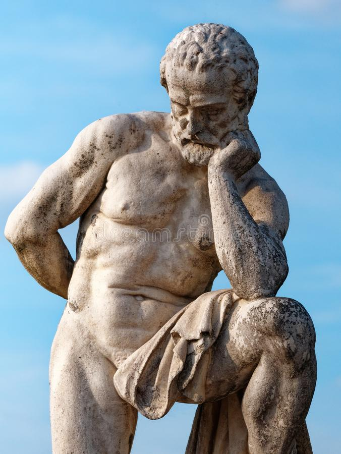 Closeup thinking man marble statue against blue sky stock photo