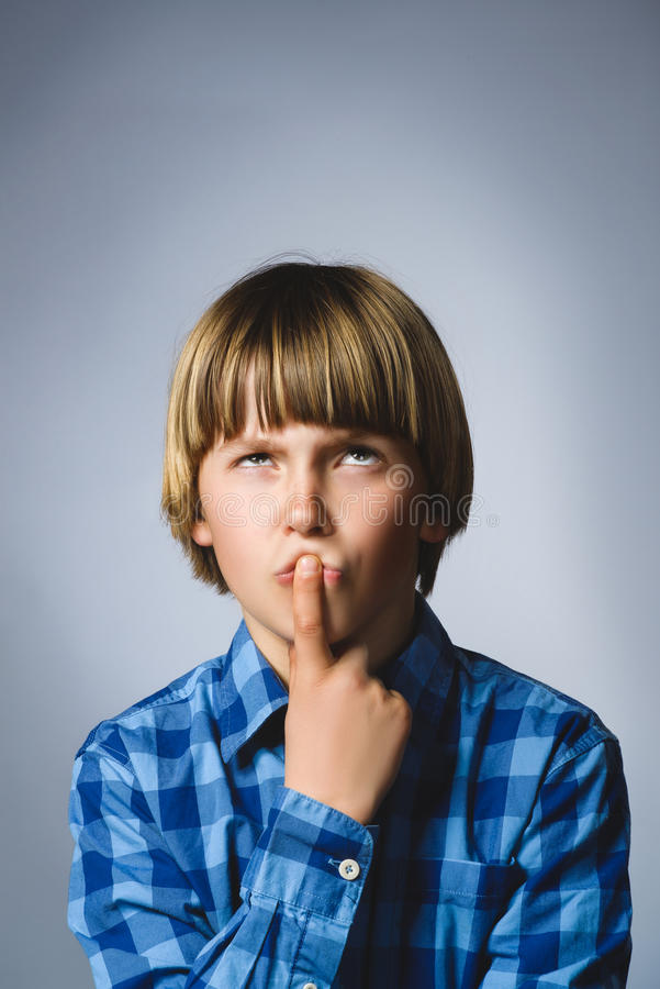 Closeup Thoughtful Young Boy Looking Up with Hand on Face Against Gray Background stock photos