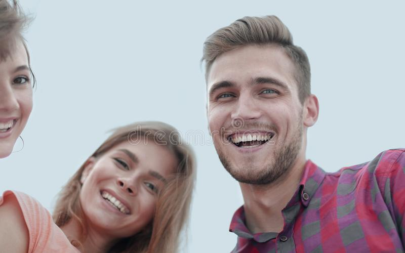 Closeup of three young people smiling on white background royalty free stock photos