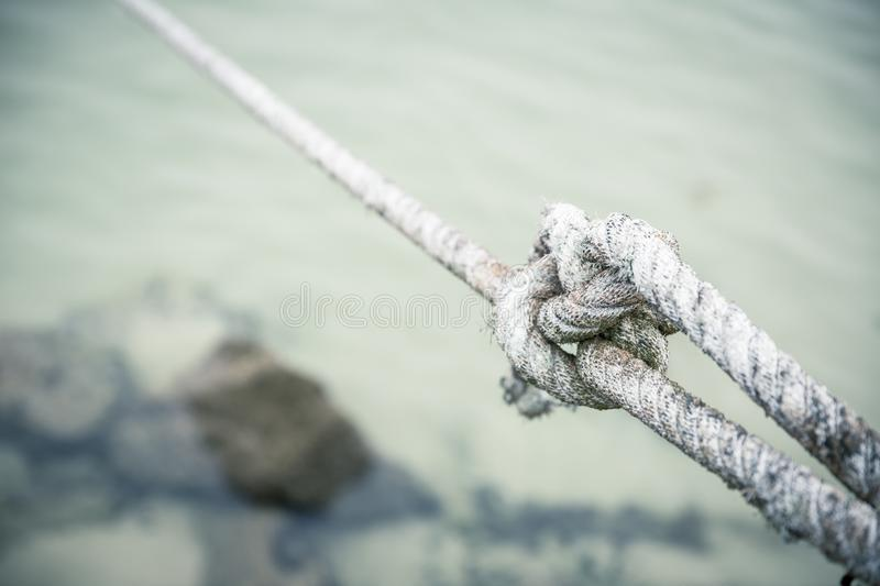 Closeup of a tightly tied up knot with a white rope tied by a fisherman royalty free stock images