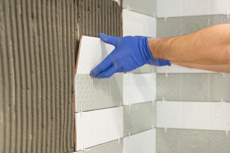 Closeup of tiler hand laying ceramic tile on wall in kitchen, renovation, repair, construction.  stock image