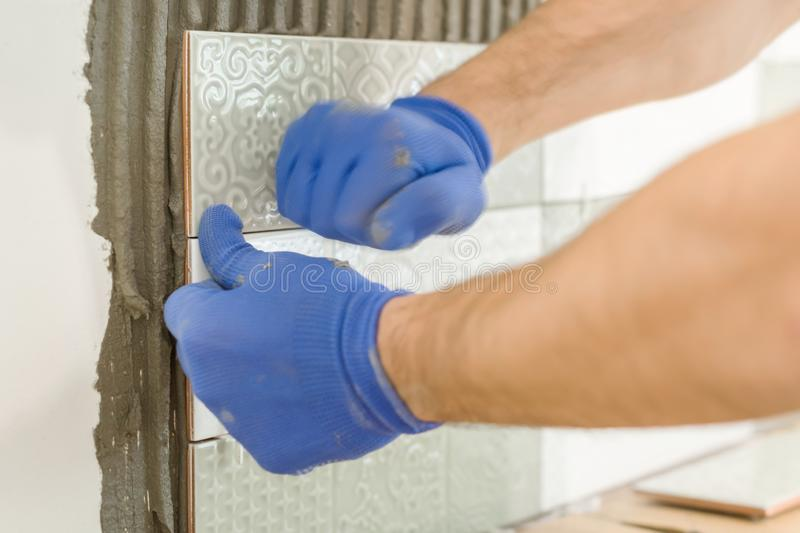Closeup of tiler hand laying ceramic tile on wall in kitchen, renovation, repair, construction stock photos