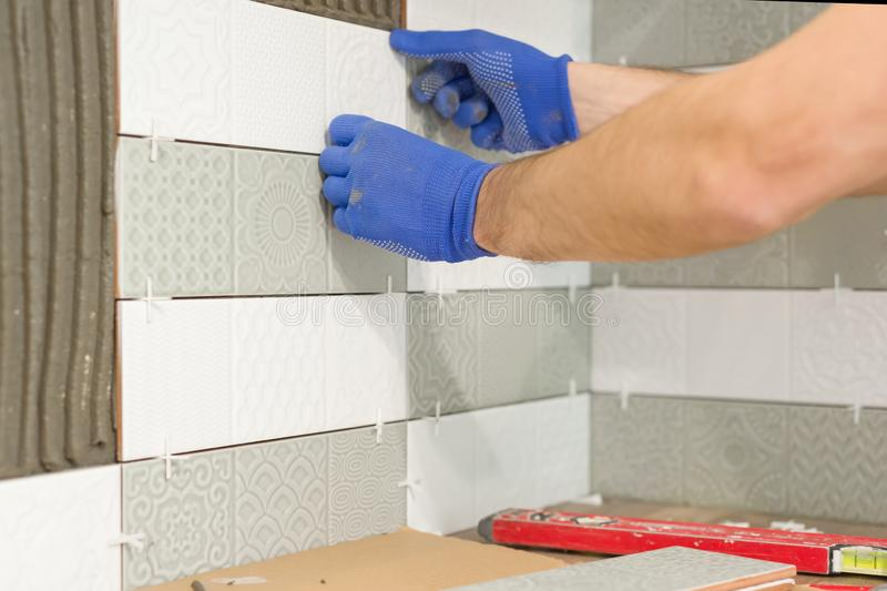 Closeup of tiler hand laying ceramic tile on wall in kitchen, renovation, repair, construction stock images