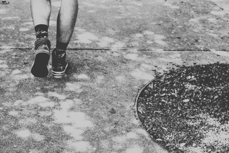 Closeup till manlig fot som går på cement med smuts på sidoskottet i svartvitt arkivbilder