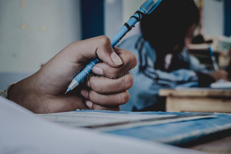 Closeup to hand of student holding pen and taking exam in classroom with stress for education test. stock photo