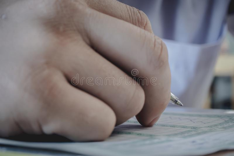 Closeup to hand of student holding pen and taking exam in classroom with stress for education test. stock images